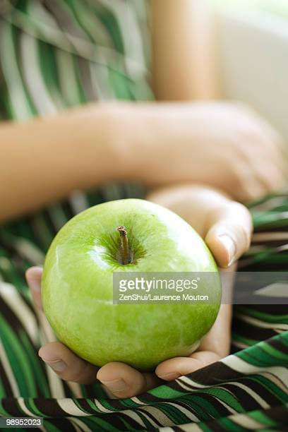 Woman holding green apple, cropped