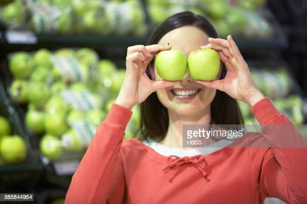 Woman holding green apples over eyes