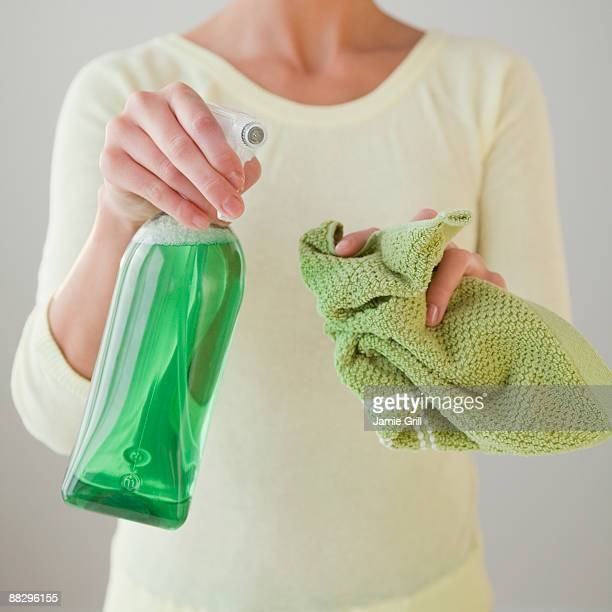 Woman holding green cleaning products
