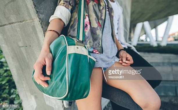 Woman holding green shoulder bag, partial view