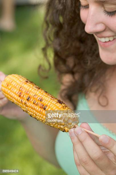 woman holding grilled corn on the cob - indian corn stock photos and pictures