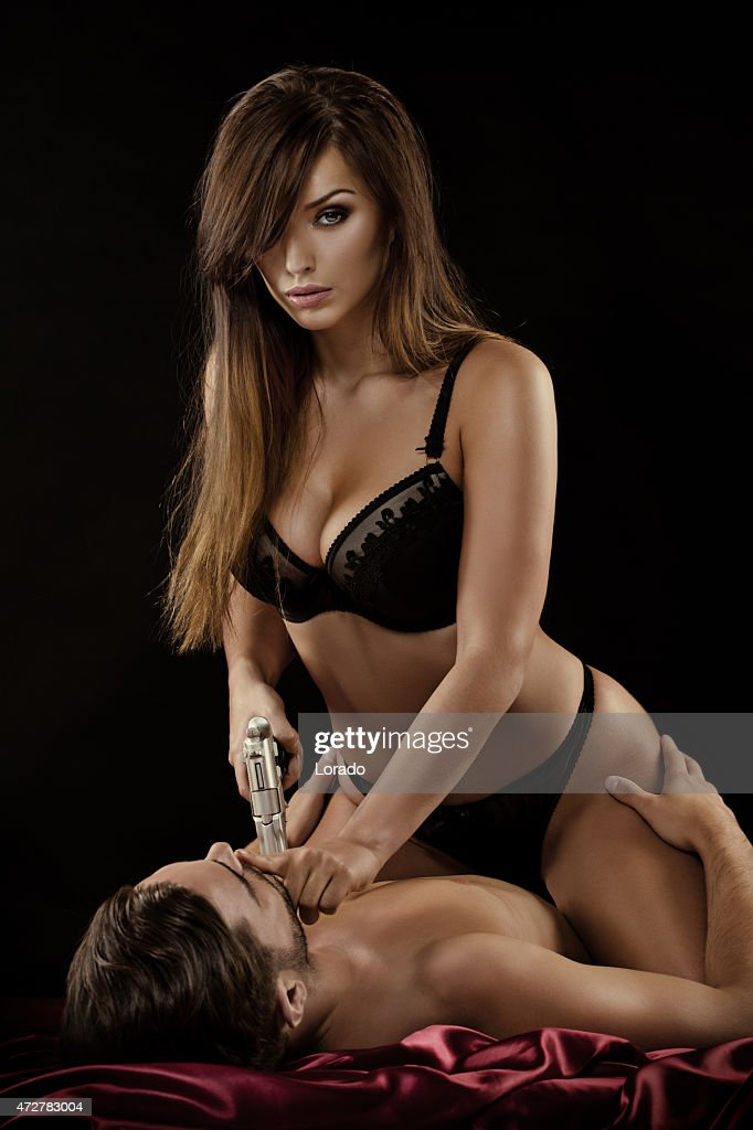 Mulher segurando arma homem sentado na cama, : Foto de stock