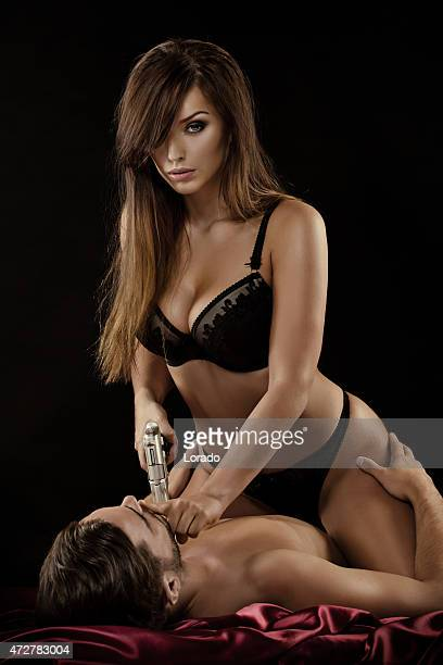 woman holding gun sitting on man in bed