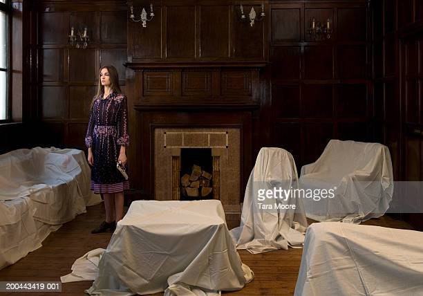 Woman holding gun standing in room with furniture covered in sheets