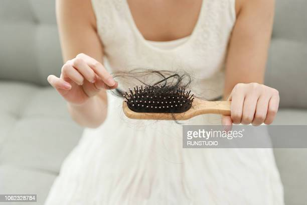 Woman holding hairbrush with lost hair