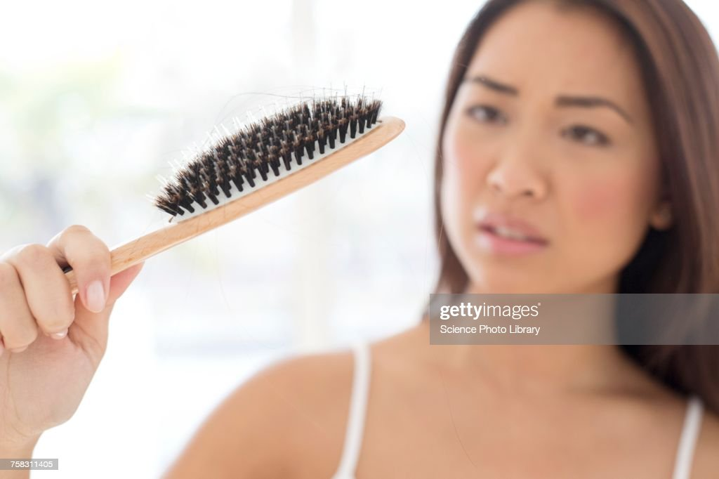 Woman holding hairbrush with worried expression : Stock Photo