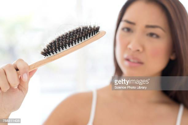 Woman holding hairbrush with worried expression