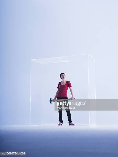 Woman holding hammer in glass cabinet