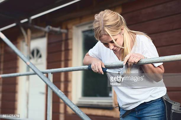 Woman holding hammer while leaning on scaffolding outside house being renovated