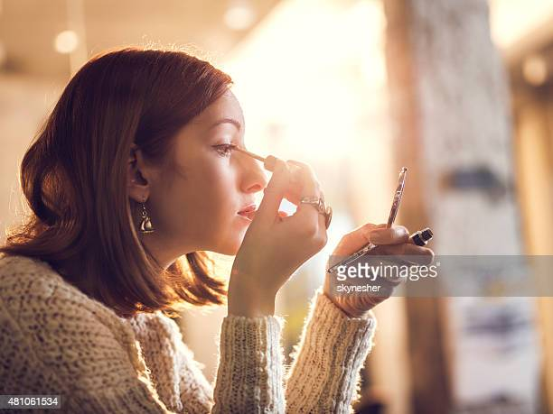 woman holding hand mirror and fixing make-up. - eye liner stock photos and pictures