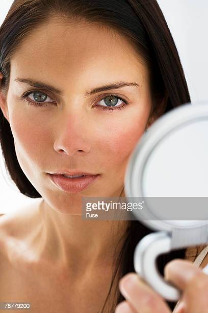 woman holding hand mirror - powder compact stock pictures, royalty-free photos & images