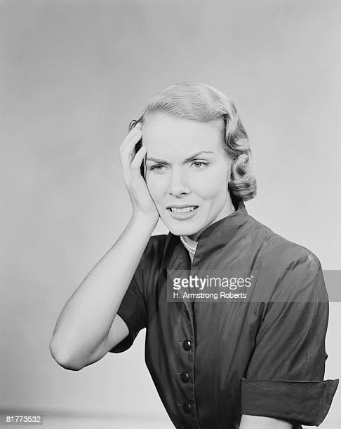 woman holding hand to her head, looking concerned. (photo by h. armstrong roberts/retrofile/getty images) - donna mezzo busto bianco e nero foto e immagini stock