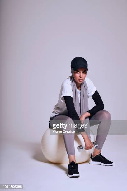 Woman holding hand weight while sitting on fitness ball