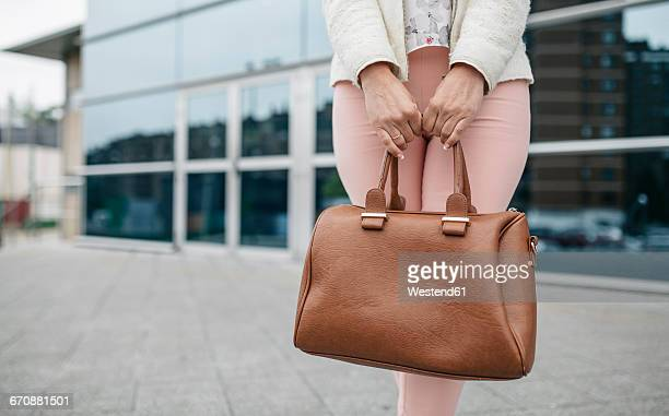 woman holding handbag in front of office building - handbag stock pictures, royalty-free photos & images