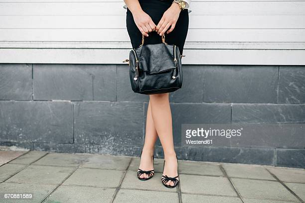 Woman holding handbag standing in front of wall