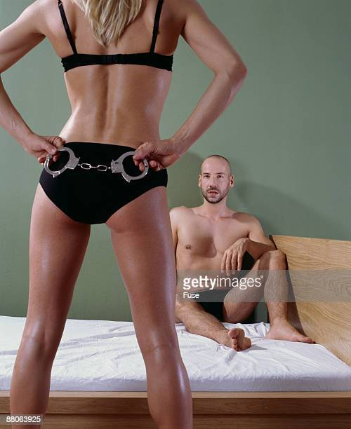 Woman Holding Handcuffs Behind Back