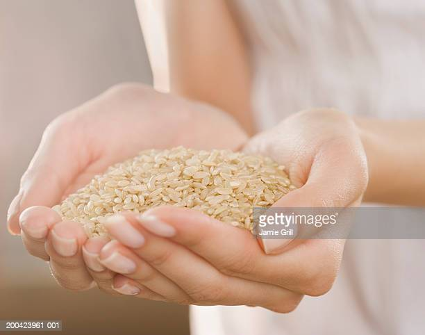 woman holding handful of brown rice, close-up - arroz integral - fotografias e filmes do acervo