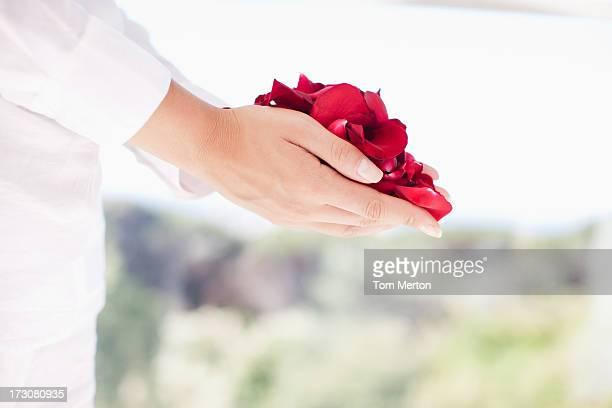 Mujer agarrando puñado de flor pétalos