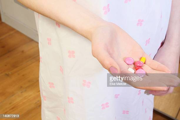 Woman holding handful of pills