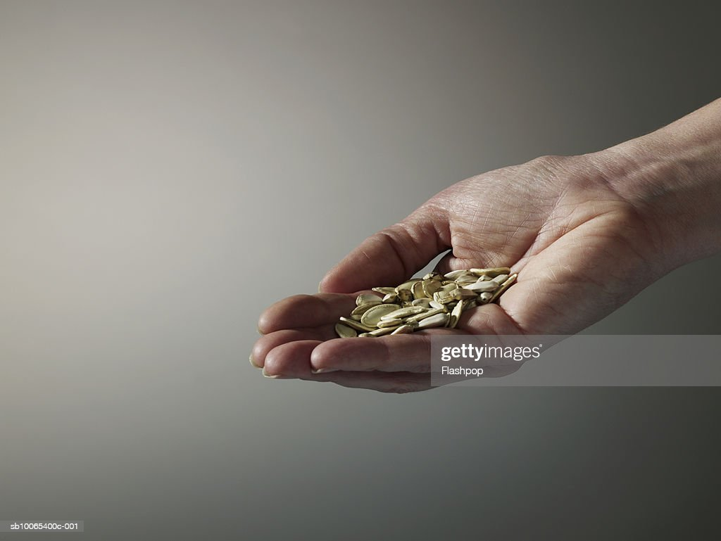Woman holding handful of seeds, close-up of hand : Foto stock