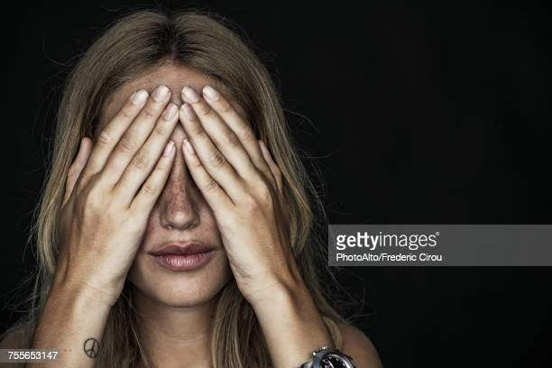 woman holding hands over eyes - hands covering eyes stock pictures, royalty-free photos & images