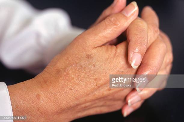 Woman holding hands together, close up of hands
