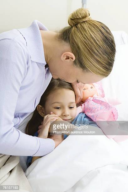 woman holding hands with daughter in hospital bed - girl in hospital bed sick stock photos and pictures