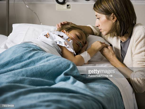 woman holding hands with young girl in hospital - patient on ventilator stock pictures, royalty-free photos & images