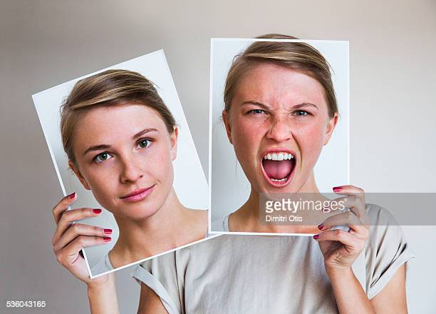 woman holding happy and angry portraits - furioso foto e immagini stock