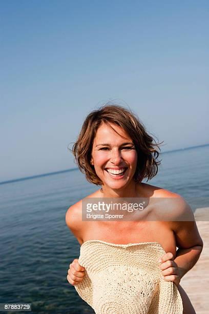 woman holding hat in front her - pechos de mujer playa fotografías e imágenes de stock