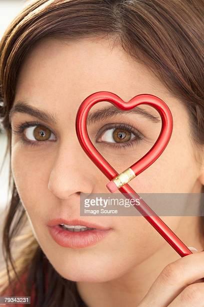 Woman holding heart shape pencil
