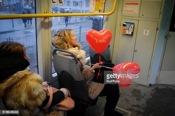 A woman holding heart shaped balloons is seen in a tram on Valentines Day in Warsaw Poland on February 14 2018