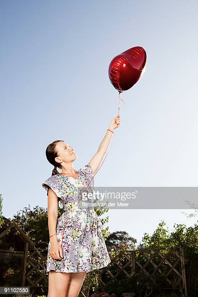 woman holding heartshaped balloon. - brown hair stock pictures, royalty-free photos & images