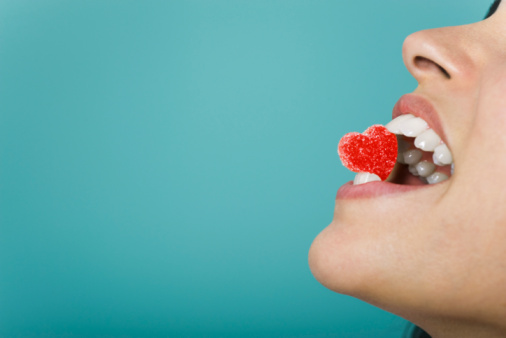 Woman holding heart-shaped candy between teeth, cropped - gettyimageskorea