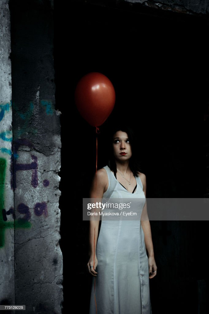Woman Holding Helium Balloon While Standing By Wall : Photo