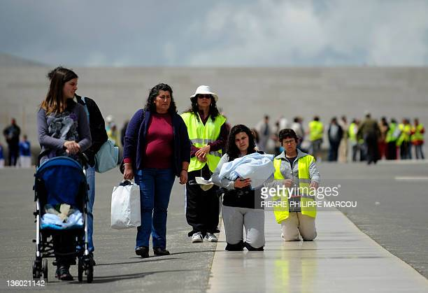 A woman holding her baby arrives at Fatima's Sanctuary on May 11 2010 Pope Benedict XVI landed in Lisbon to begin a fourday visit included Fatima and...