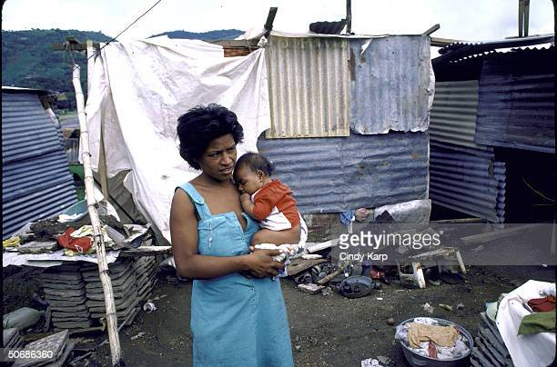 Woman holding her baby outside their metal shack