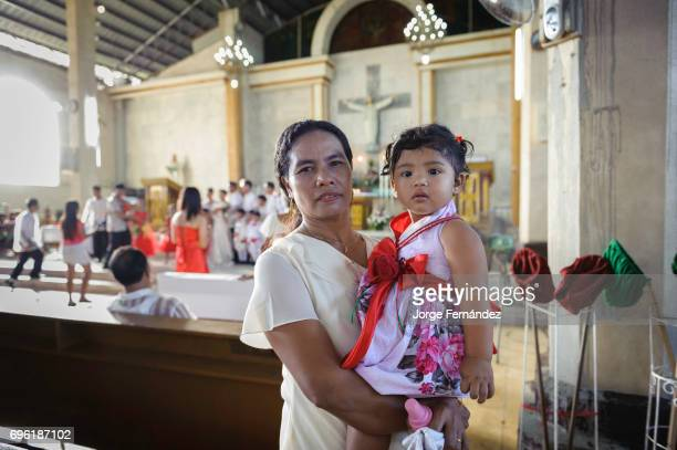 Woman holding her daughter inside a Catholic church during a wedding