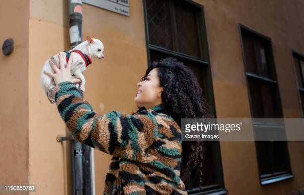 woman holding her dog up in the air smiling - female hairy arms stock photos and pictures