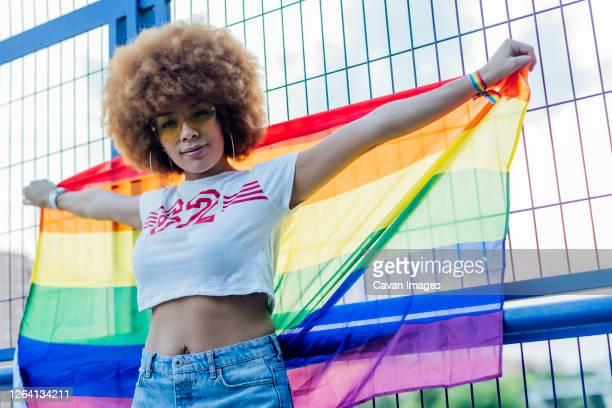 woman holding her gay pride flag on a bridge - バイセクシャル ストックフォトと画像