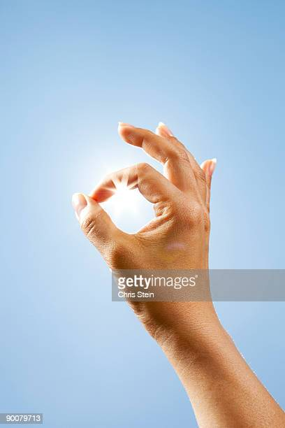 Woman holding her hand to the sun