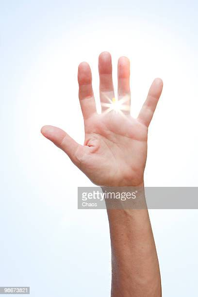 woman holding her hand up to the sun - newhealth stock photos and pictures
