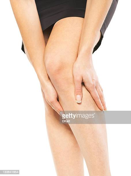 a woman holding her knee in pain - feet torture stock pictures, royalty-free photos & images