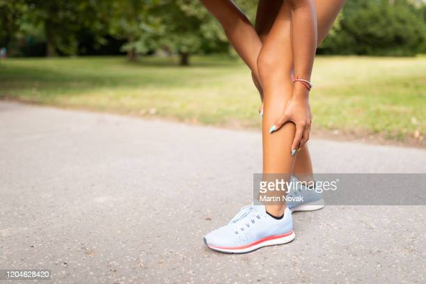 woman holding her leg due to muscle tear in calf - cramp stock pictures, royalty-free photos & images