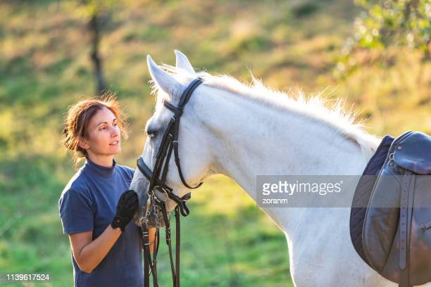 woman holding her mare and looking at it - rein stock pictures, royalty-free photos & images