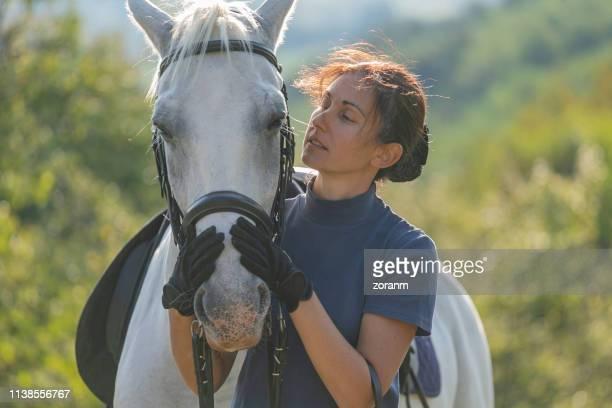 frau hält die schnauze ihrer stute mit zuneigung - racehorse stock-fotos und bilder