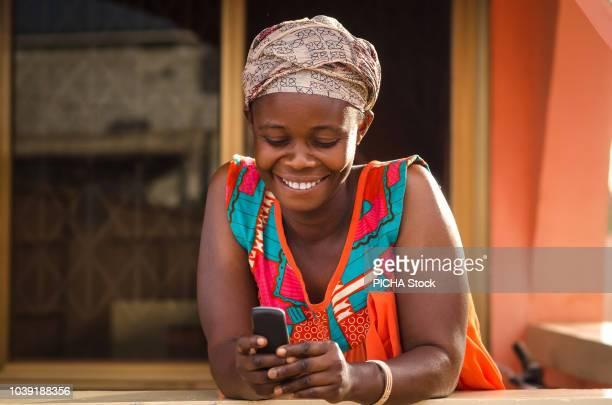 woman holding her mobile phone - ghana africa fotografías e imágenes de stock