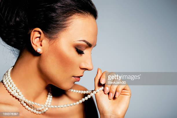 A woman holding her pearl necklace