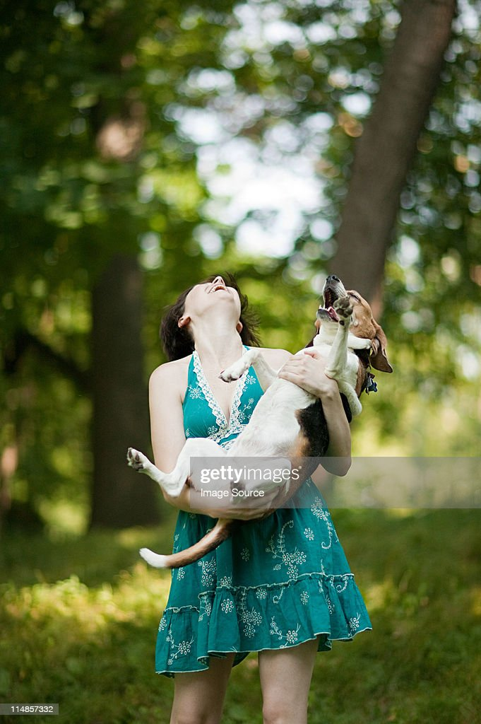 Woman holding her pet beagle : Stock Photo