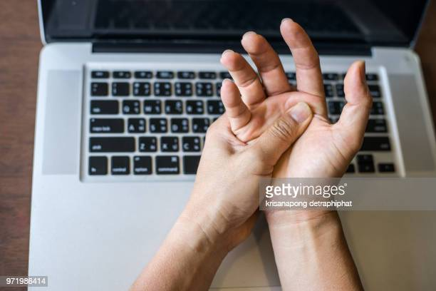woman holding her wrist pain from using computer.,hand pain - wrist stock pictures, royalty-free photos & images